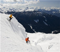 Skiers enjoying Whistler mountain with Black Tusk in the background